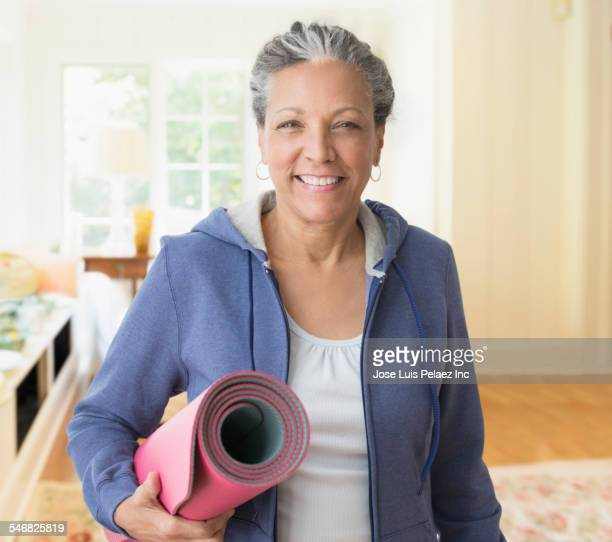 older hispanic woman carrying exercise mat - opgerold samenstelling stockfoto's en -beelden