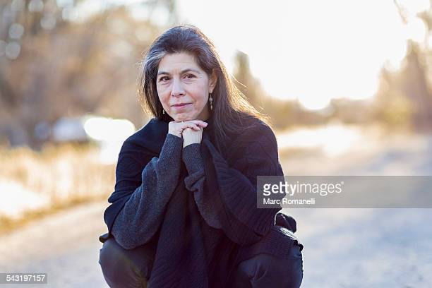 older hispanic woman crouching outdoors - one mature woman only stock pictures, royalty-free photos & images