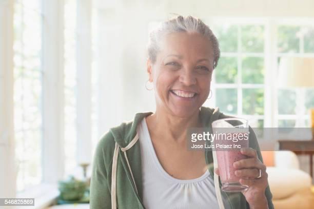 Older Hispanic woman drinking fruit smoothie