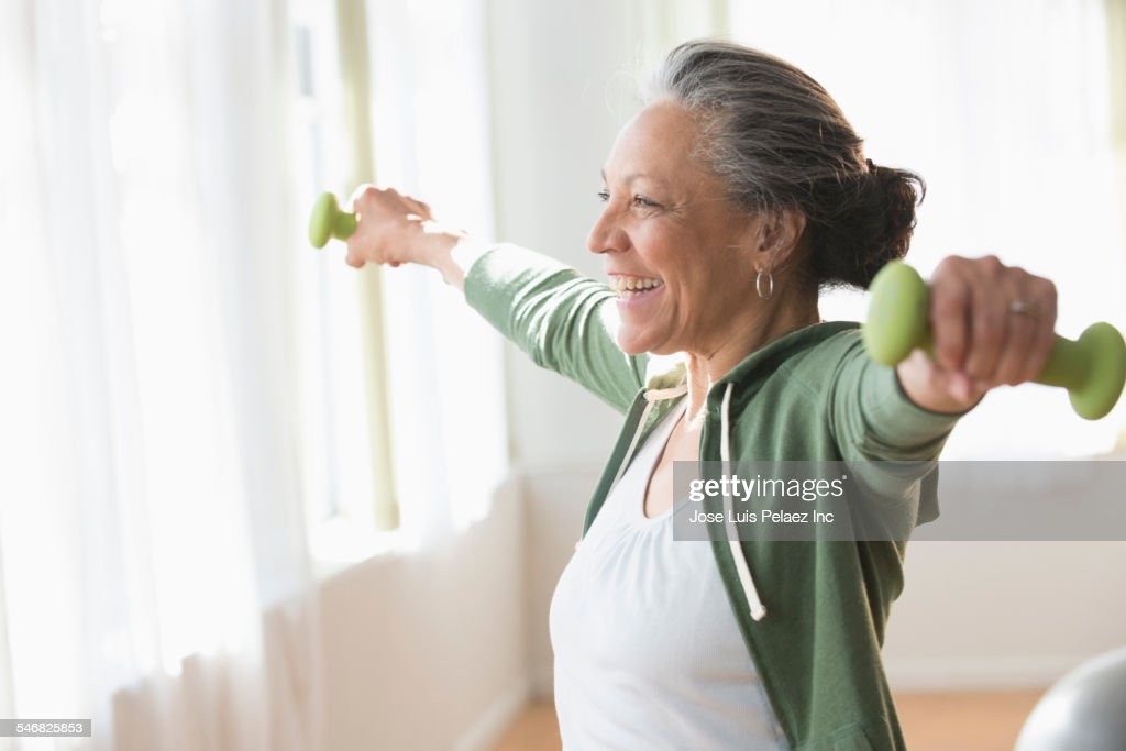 Older Hispanic woman lifting weights in living room : Stock Photo