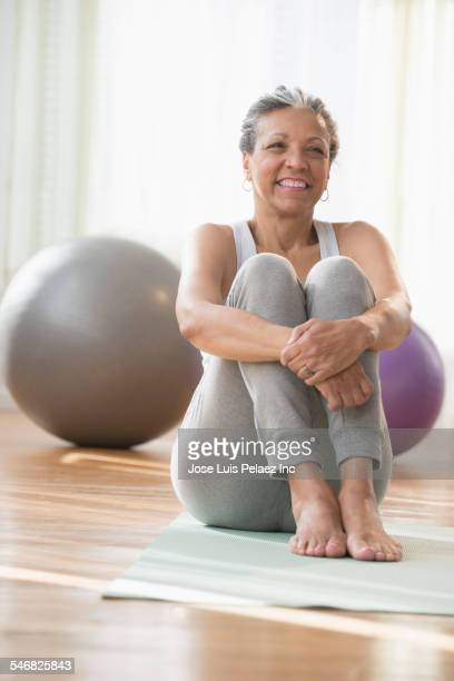 older hispanic woman sitting on exercise mat - one senior woman only stock pictures, royalty-free photos & images