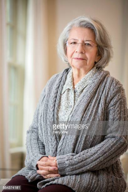 Older Hispanic woman sitting with hands clasped
