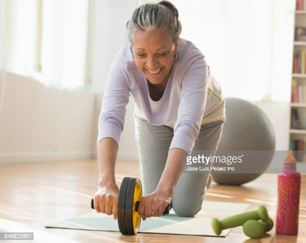 Older Hispanic woman working out on exercise mat