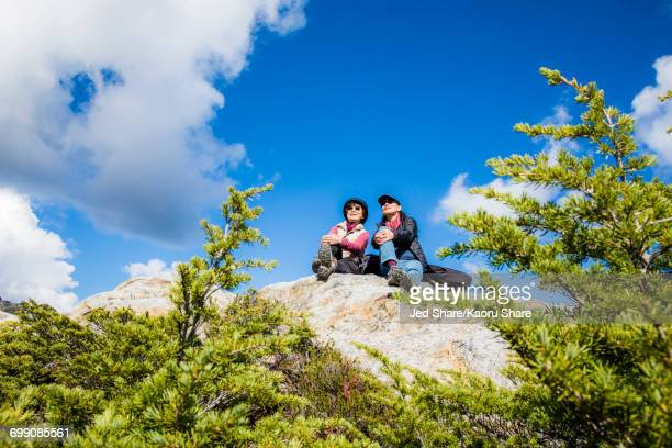 Older Japanese mother and daughter sitting on rock
