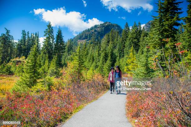 Older Japanese mother and daughter walking on nature path