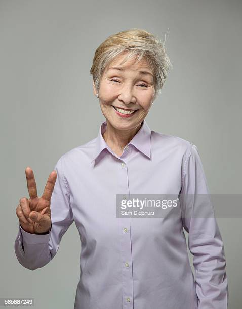 Older Japanese woman making peace sign