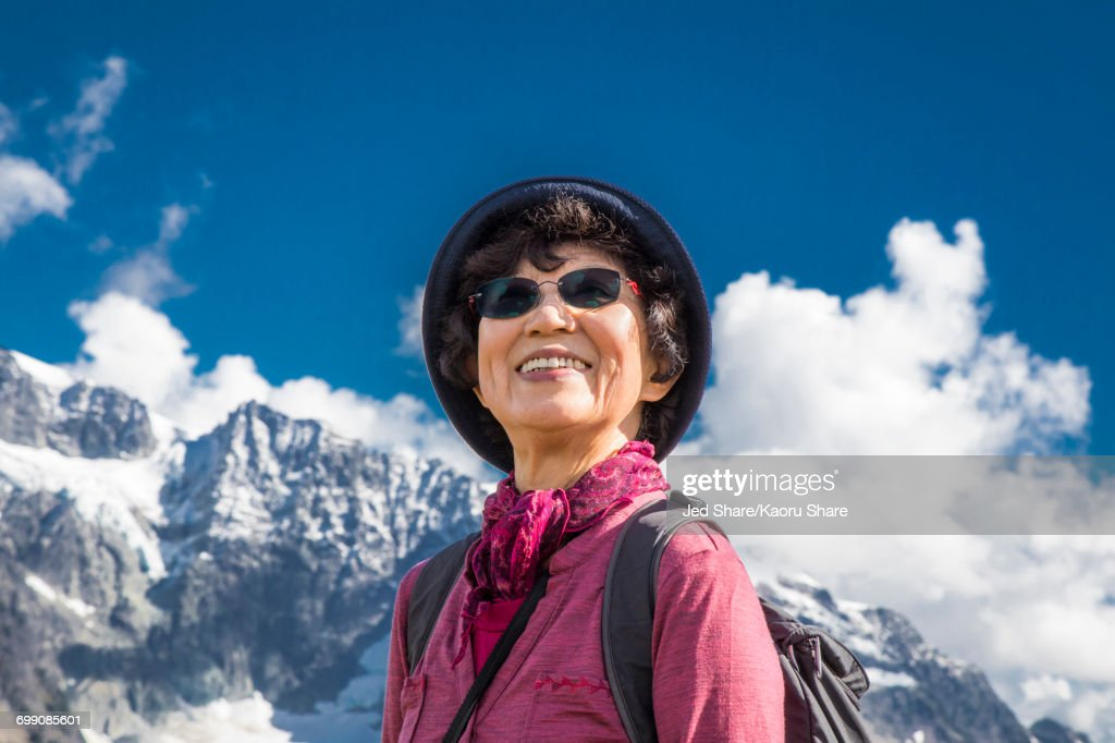 Older Japanese woman smiling near mountain : ストックフォト