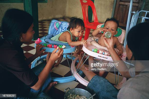 Older kids feed toddlers a thin gruel of rice porridge with bits of smoked fish for lunch at the Chea Sim Orphanage There are 55 small children and...