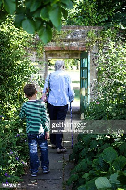 Older lady and boy leaving walled garden