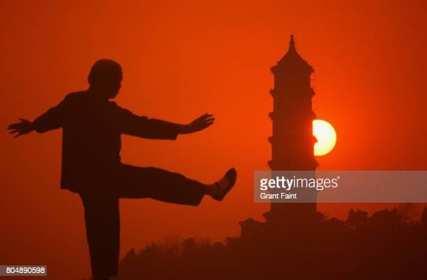 Older lady doing Tai Chi exercising at sunset.