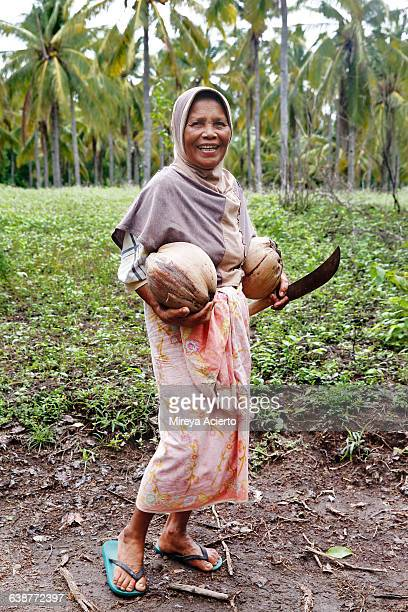 Older, local woman holding coconuts and machete