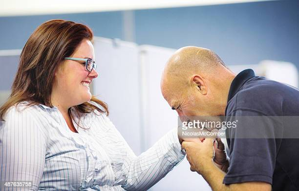 Older male office worker kisses hand of amused  female colleague