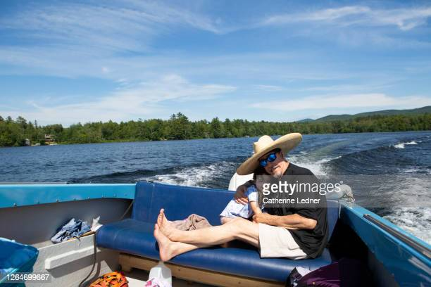older man and 3 year old girl hugging while riding in the back seat of a motorboat on a sunny summer day in maine - catherine ledner stock pictures, royalty-free photos & images
