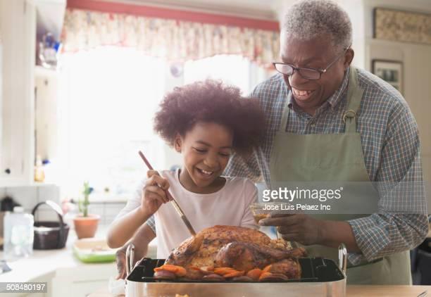 Older man and granddaughter cooking together in kitchen