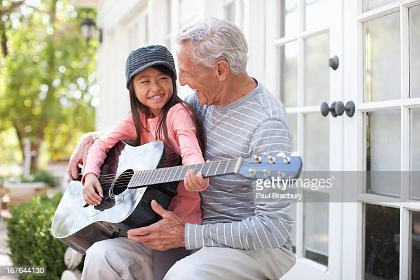 Plus Homme jouant de la guitare et petite-fille