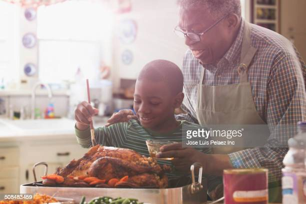 Older man and grandson cooking together in kitchen
