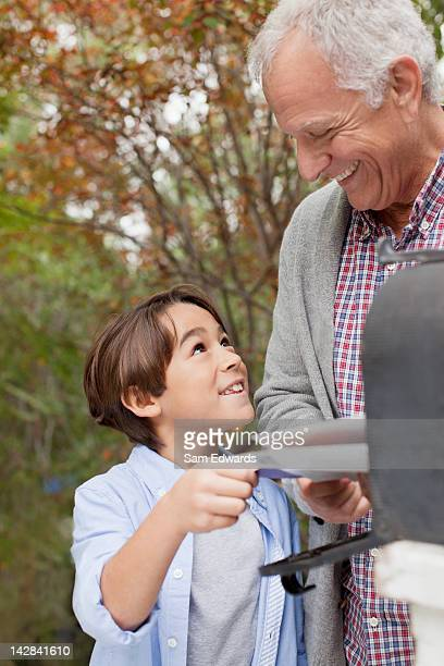Older man and grandson opening mailbox