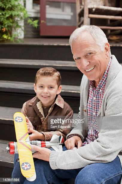 Older man and grandson playing with model plane