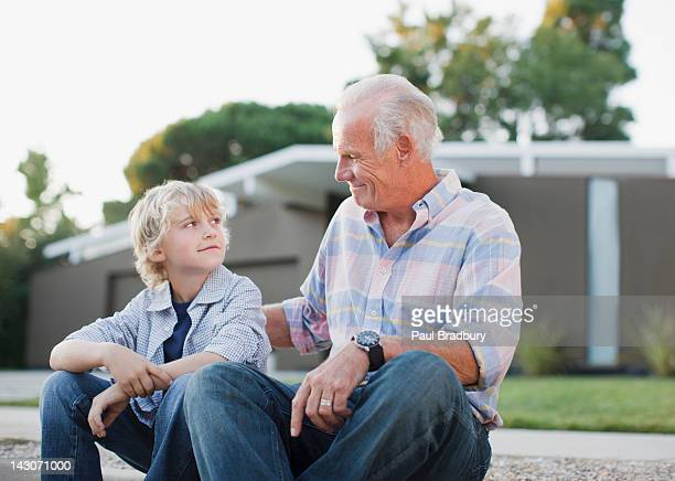 older man and grandson sitting together - generation gap stock pictures, royalty-free photos & images