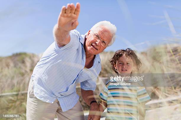 Older man and grandson standing outdoors