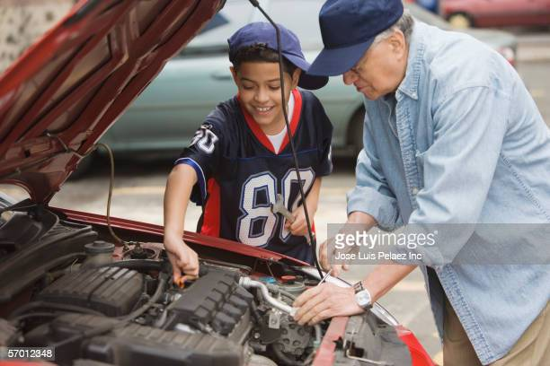 Older man and his grandson working on a car