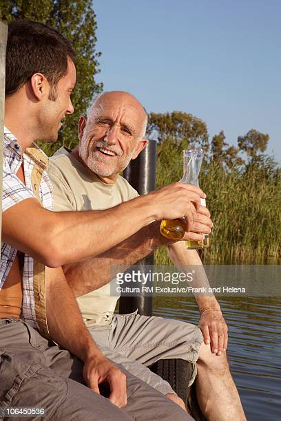 Older man and son drinking beer on jetty