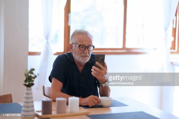 older man and technology use - foco diferencial imagens e fotografias de stock