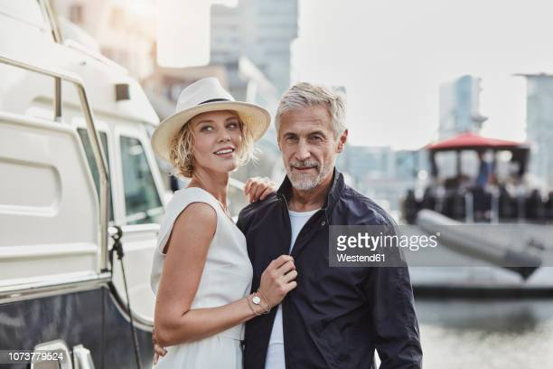 older man and young woman at a marina next to a yacht - may december romance stock photos and pictures