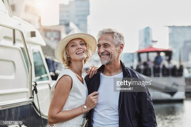 older man and young woman at a marina next to a yacht - elegance stock pictures, royalty-free photos & images