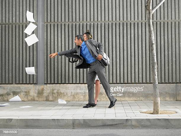 Older man and young woman chasing papers blown by the wind down the pavement, Alicante, Spain,