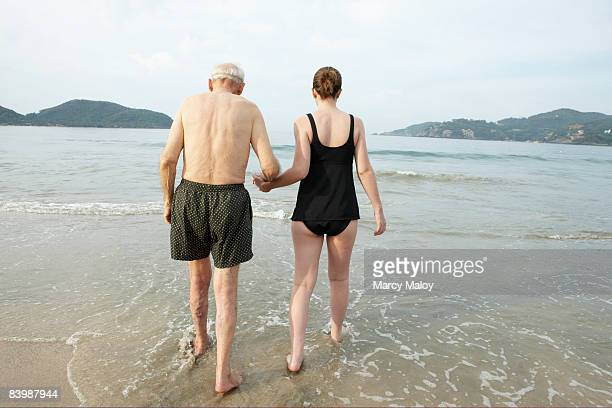 Older man and young woman walking in the ocean.