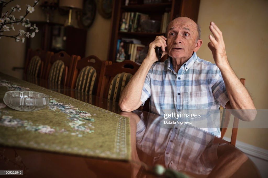 Older man arguing on phone : Stock Photo