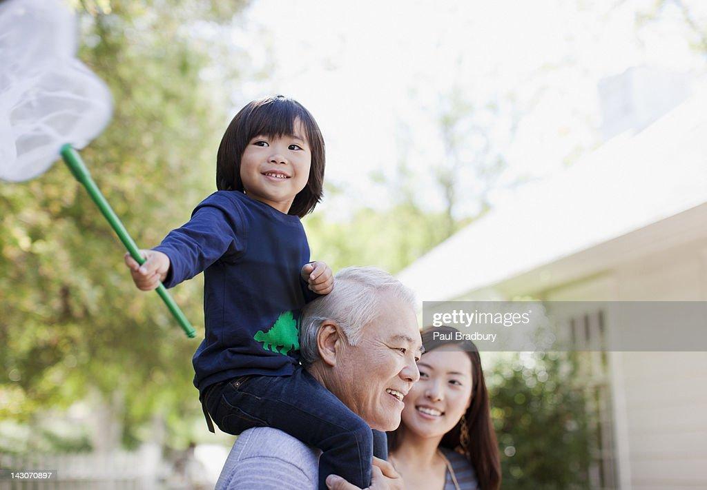 Older man carrying grandson on shoulders : Stock Photo