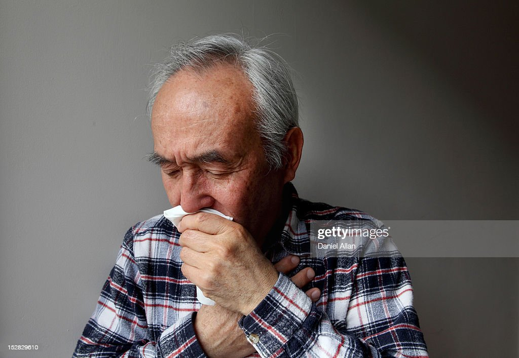 Older man coughing into napkin : Stock Photo