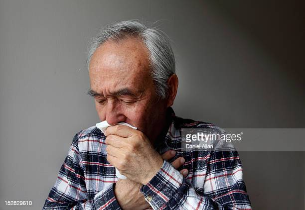 older man coughing into napkin - cough stock pictures, royalty-free photos & images