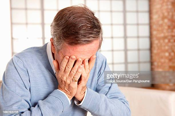 Older man covering face with hands