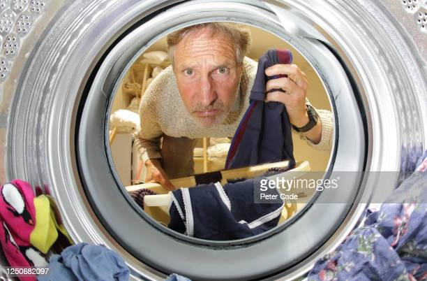 older man doing the laundry, looking into washing machine - spinning stock pictures, royalty-free photos & images