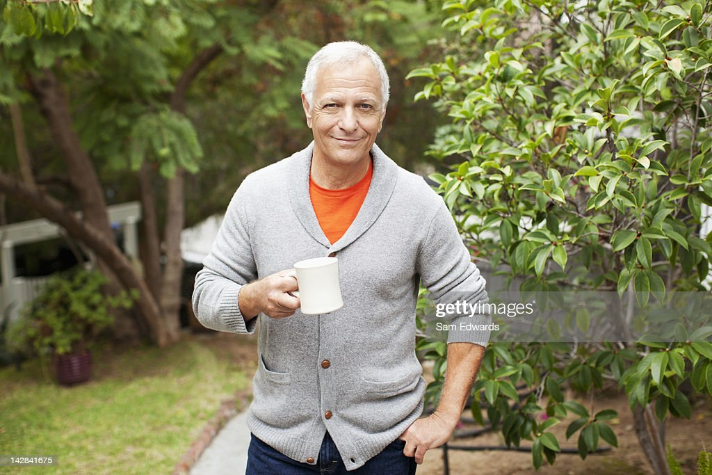 Older man drinking cup of coffee outdoors : Stock Photo