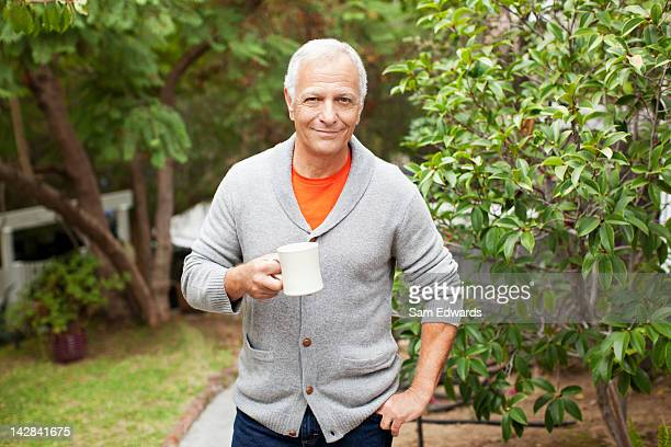 Older man drinking cup of coffee outdoors