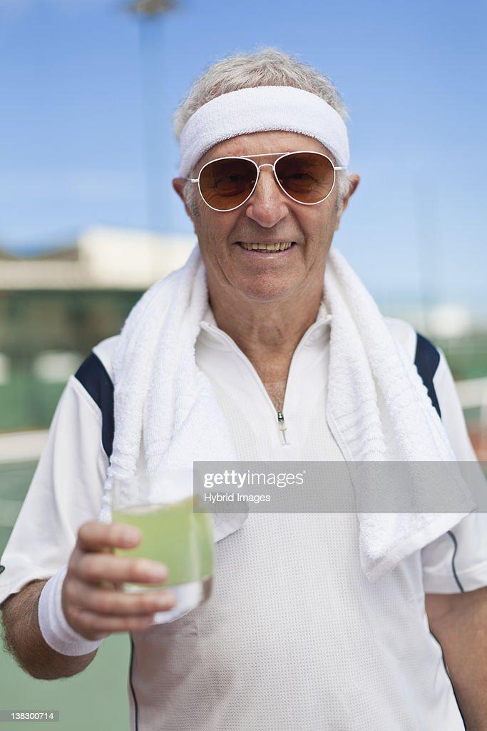 Older man drinking lemonade outdoors : Stock Photo