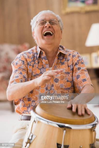Older man drumming on a bongo