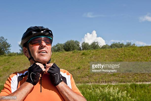 older man fastening bike helmet - headwear stock pictures, royalty-free photos & images