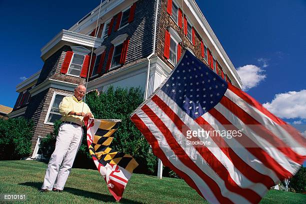 Older man hanging American and state flags