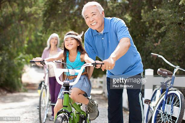 older man helping granddaughter ride bicycle - granddaughter stock pictures, royalty-free photos & images