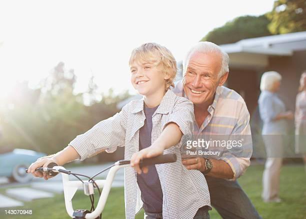 Ältere Mann helfen Enkel mit dem Fahrrad