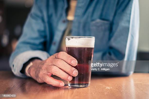 Older man holding glass for beer