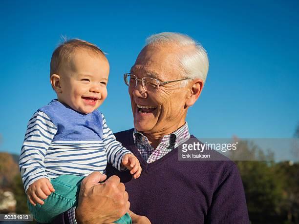 Older man holding grandson outdoors