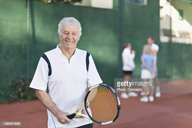 Older man holding tennis racket on court