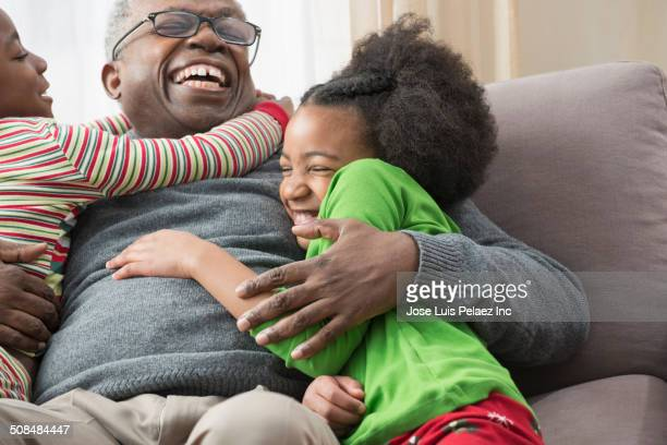 Older man hugging grandchildren on sofa