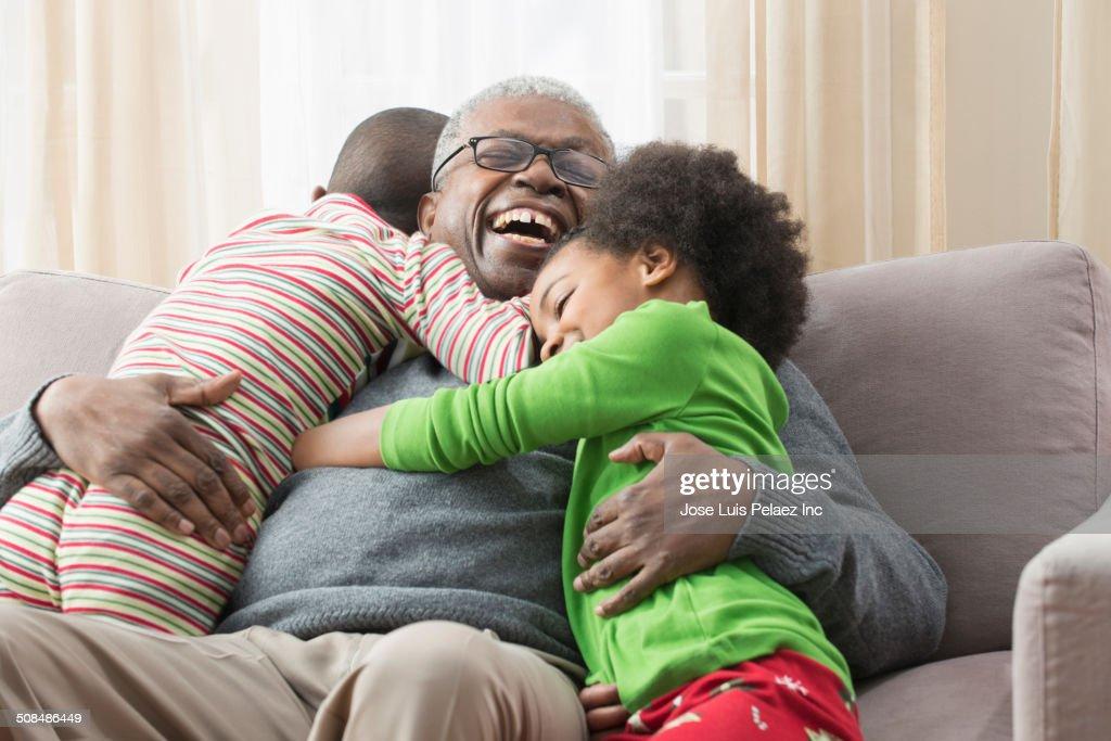 Older man hugging grandchildren on sofa : Stock Photo